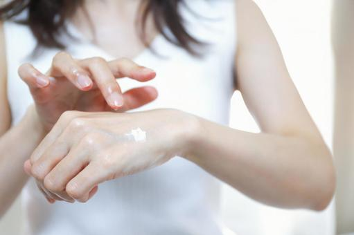 Women's hands applying cream