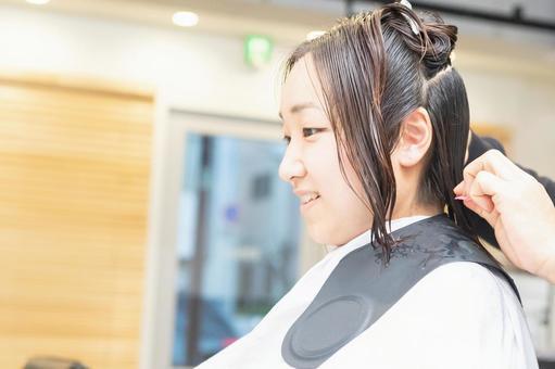 미용실에서 머리를 잘라달라고 젊은 여성
