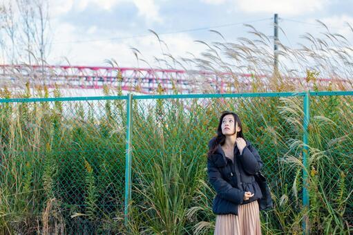 울타리 앞에 서서 하늘을 바라 보는 여성