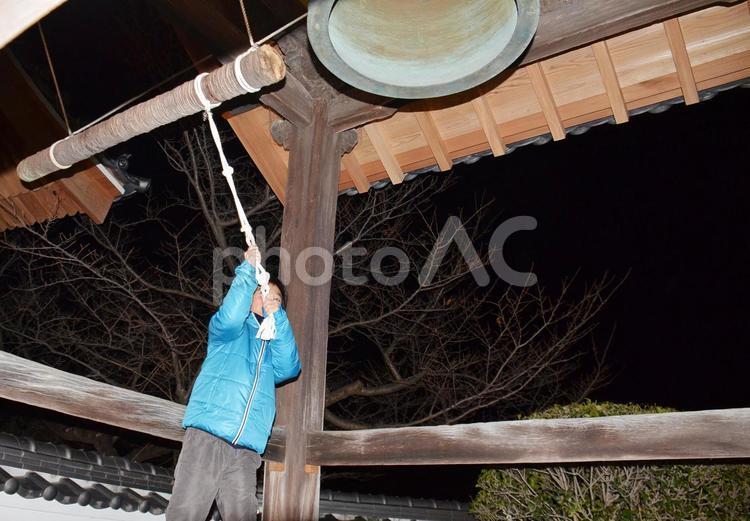 除夜の鐘を打つ男の子の写真