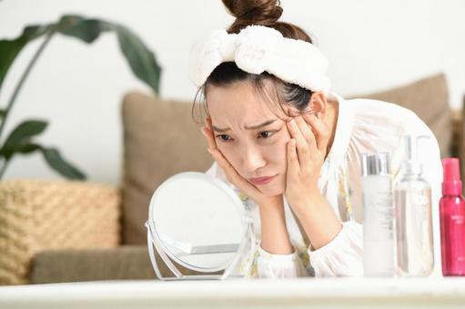 거울을 보면서 피부 트러블로 고민하는 여성