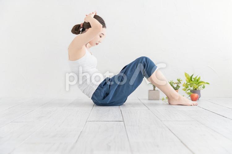 筋トレ(腹筋)をする女性の写真