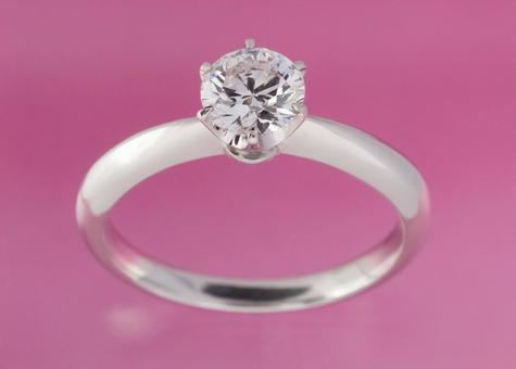 Close-up shot of a diamond ring on a pink background