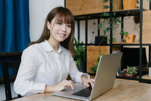 Chinese woman using a laptop at the dining table