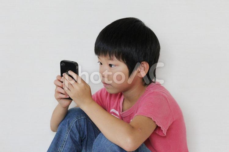 スマホで遊ぶ男の子の写真