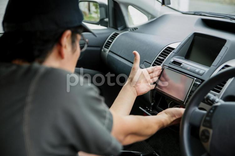 カーナビ・オーディオを取り付ける整備士の写真
