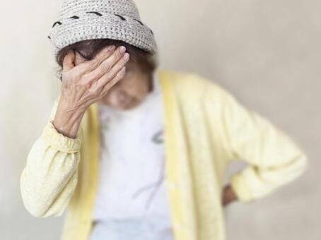Elderly woman putting her hand on her forehead