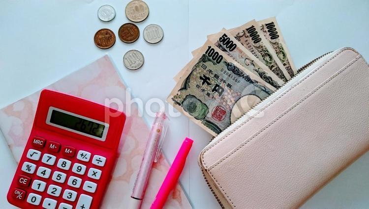 現金と電卓とノートの写真