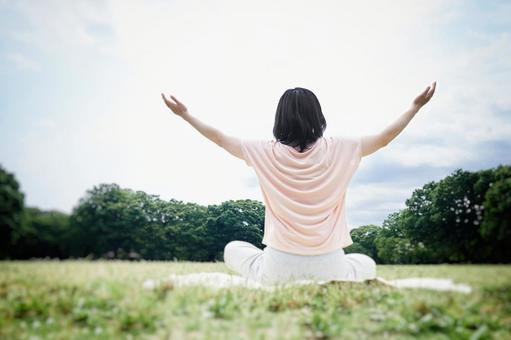A woman meditating on a natural lawn