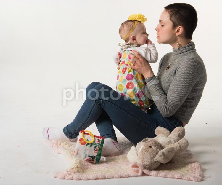 床に座って赤ちゃんを抱っこするお母さん20の写真