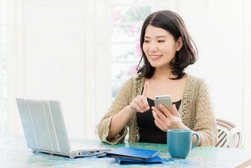 一個操作計算機和智能手機的女人