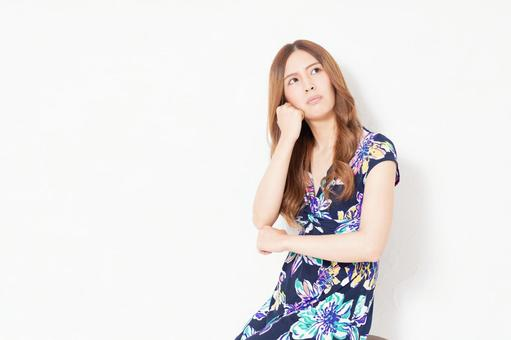 A young woman in a blue dress thinking in front of a white wall