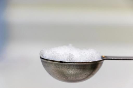 White sugar on a measuring spoon