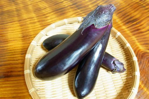 Delicious eggplant in a colander, three fresh eggplants