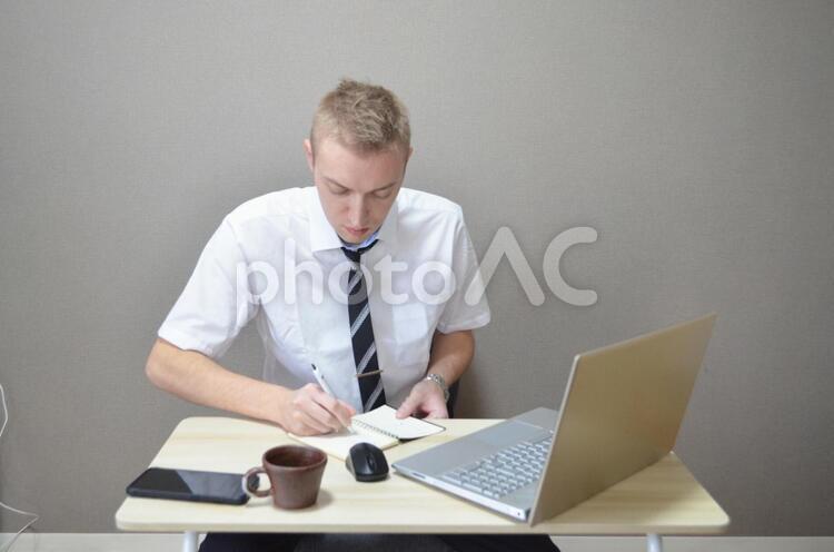 メモを書いているビジネスマンの写真