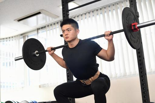 A man squatting in the gym