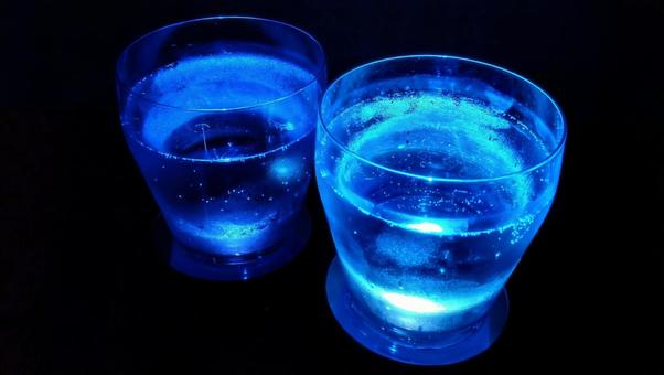 A glass of lighted blue carbonated drink