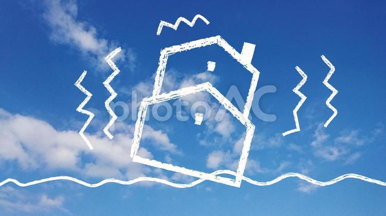 青空に地震で揺れる家の写真