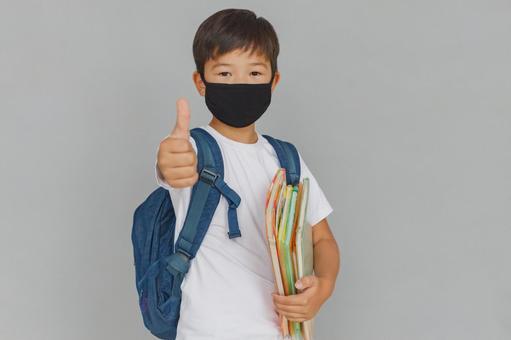 戴著面具,拿著一本教科書的小學男孩