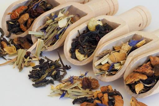 Herbal tea leaves lined up with a wooden spoon