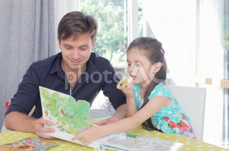 女の子に絵本を読み聞かせる男性2の写真