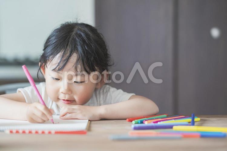 ダイニングテーブルでお絵かきに集中する子供の写真
