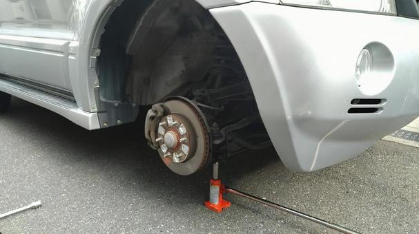 Jacking up the front wheels of the SUV, checking the brakes and changing tires