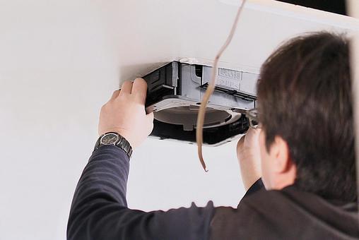 Electrician replacing the ventilation fan