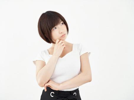 A woman who puts her hand on her chin on a white background and wonders which is better