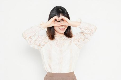 A young woman in a lace blouse standing in front of a white background and making a heart shape by hand