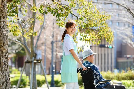 A care helper woman taking a walk outdoors and a senior man in a wheelchair