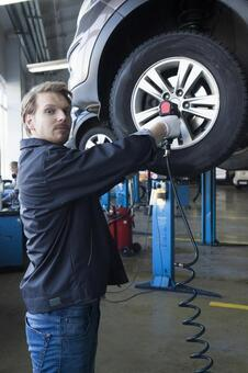 Automobile mechanic servicing tires 13