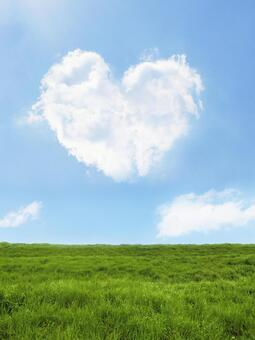 Heart-shaped clouds, blue sky and grassland-portrait composition