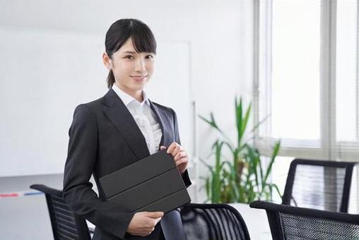 Japanese female business woman holding a tablet in the office