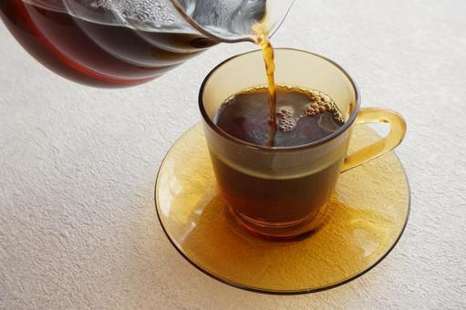 將咖啡倒入琥珀色的杯子中