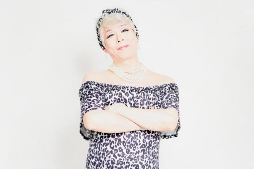 Drag queen standing in front of a white background and folding her arms