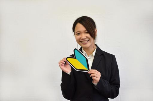 Female employee smiling with a beginner mark in hand