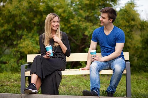 Couple sitting on the bench and drinking a drink 4