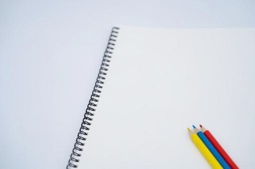 Blank notebook and colored pencils