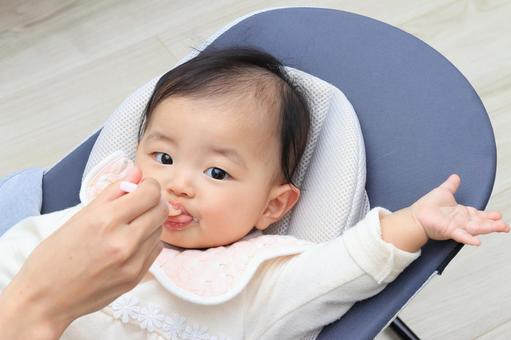 거실에서 이유식을 먹여주고있는 아기