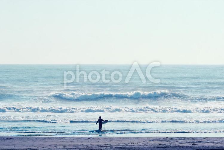 波に向かうサーファーの写真