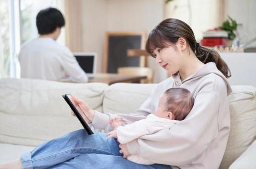재택 근무를하는 남편과 태블릿을 보는 아내