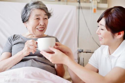 介護士からマグカップを受け取るおばあちゃん4