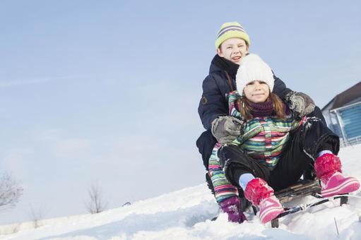 女孩和男孩1名乘坐雪橇
