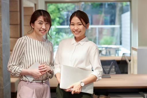 Two women standing with a laptop or tablet