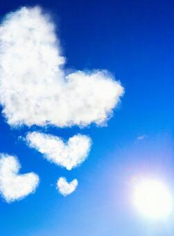 Blue sky, dazzling sun and heart cloud