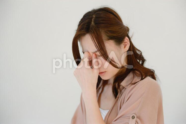 眉間を抑える女性1の写真