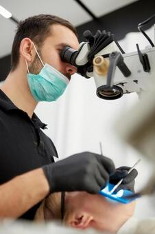 Male dentist with microscope treatment 5