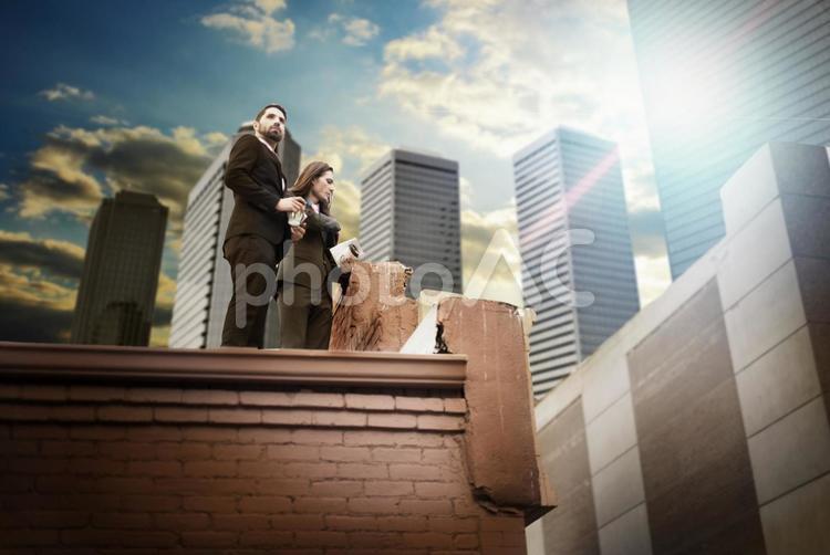崩れたビルの屋上にいるスーツの男女の写真
