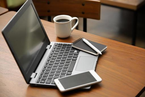 A desk with a computer and a smartphone